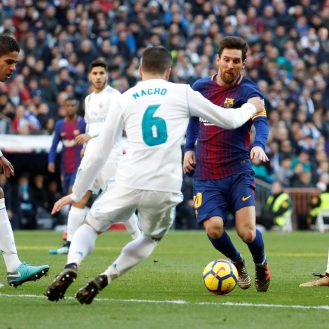 Soccer Football - La Liga Santander - Real Madrid vs FC Barcelona - Santiago Bernabeu, Madrid, Spain - December 23, 2017   Barcelona's Lionel Messi in action with Real Madrid's Raphael Varane and Nacho    REUTERS/Paul Hanna